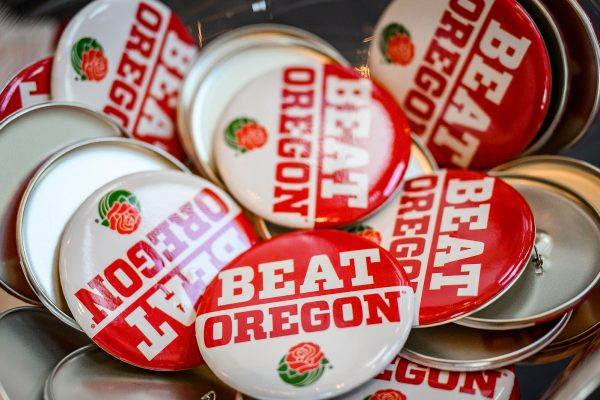 Pins with the words Beat Oregon with a Rose Bowl rose beneath it