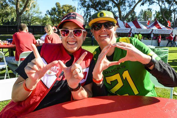 Badger fan Megan Rollo (left) and her wife, an Oregon fan, Jordan Wilde hang out at the Badger Huddle event